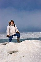 Male Inupiaq Eskimo hunter standing on a ice pressure ridge while wearing a traditional Eskimo parka Atigi and seal skin hat, Chukchi Sea near Barrow,...