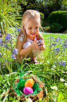 Little smiling girl finds a colourful Easter eggs in the grass
