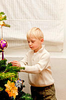 Cute blond boy decorating Christmas tree
