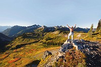 a hiker stands on a ridge with arms raised viewing the tatoosh mountains in mt. rainier national park, washington, united states of america