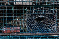 Lobster traps are stacked on top of each other in a Maine harbor.