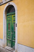 old wooden door on a yellow building, cascais, portugal
