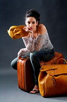 Young woman posing, sitting in a studio with two suitcases of leather and leather yellow cap, looking straight at the camera with the face of boredom,