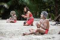 indigenous people siting on the sand clapping and singing, queensland, australia