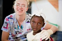 a nurse sits with a girl at a clinic, grand saline, haiti