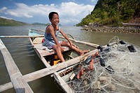 a young filipino boy smiles as he works on his family´s wooden bangka boat in the tiny fishing village of vigan near snake island and el nido, vigan, ...