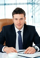 Young business executive sitting in chair attentively looking at you
