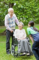 Senior man pushing senior woman on wheelchair and talking to a healthcare worker, Tokyo Prefecture, Honshu, Japan