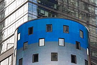 Bright blue and grey cylindrical building in front of a reflective glass skyscraper