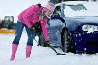 Woman shoveling snow from around car in snowfall