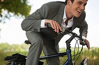 Young happy businessman riding bicycle