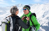 Woman fastening husband´s backpack on mountain top