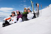Skiers sitting in snow relaxing next to skis
