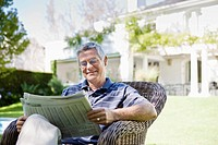 Senior man sitting in armchair, reading newspaper