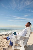 Man in bathrobe relaxing on beach