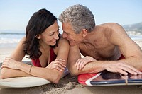 Happy couple lying on surfboards on beach (thumbnail)