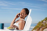 Woman talking on mobile phone on beach