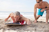Two male surfers playing on beach