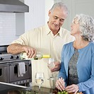Couple having white wine in kitchen