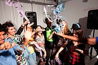 People dancing at party with streamers