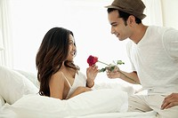 Man giving rose to woman in bed (thumbnail)