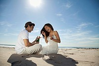 Couple drinking champagne on beach (thumbnail)