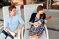 Couple sitting on lounge chairs, woman playing ukelele