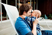 Father with baby son sitting on lounge chair