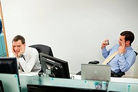 Businessman using smartphone, male colleague looking sideways