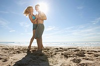 Young couple dancing on sandy beach, with bottle of champagne left in sand (thumbnail)