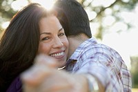Young couple embracing in bright sunshine (thumbnail)