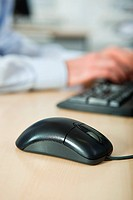 Office worker using computer, mouse in foreground (thumbnail)