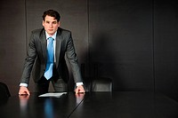 Businessman leaning on conference table with documents
