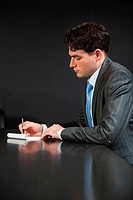 Businessman in conference room making notes