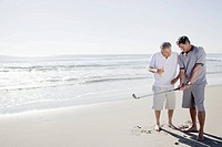 Two men playing golf on beach