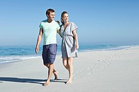 Happy couple walking on sandy beach