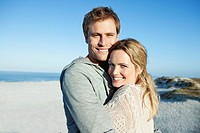 Portrait of happy couple embracing on beach