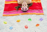 Portrait of girl 7_9 lying on beach with scuba mask, high angle view