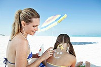 Woman applying sun cream on daughter's 10_12 back