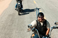 Two men riding motorcycles along road