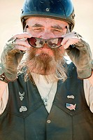 Portrait of senior motorcyclist removing sunglasses