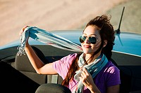 Young woman in convertible car wearing scarf and sunglasses