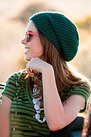 Portrait of young woman wearing knit hat and sunglasses