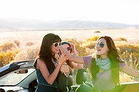 Three young women by convertible car