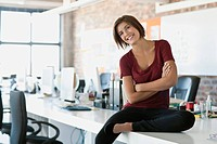Portrait of smiling woman sitting on desk in office