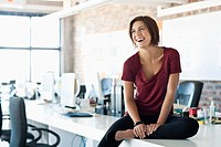 Smiling woman sitting on desk in office (thumbnail)