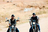 Two men riding motorcycles on road