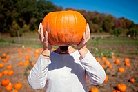 Person holding a pumpkin in front of face