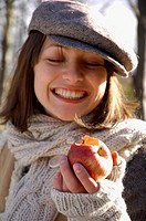 OUTDOORS IN AUTUMN, A YOUNG WOMAN BITING INTO AN APPLE
