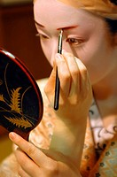 A GEIKO'S GEISHA TRADITIONAL MAKEUP DORAN, DRAWING THE EYEBROWS WITH RED AND BLACK MAKEUP, THE HAIR IS TIED BACK TO GO UNDER A WIG KATSURA, GION DISTR...